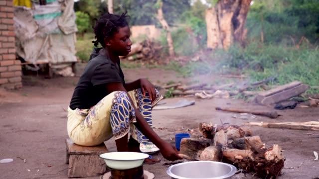 農村、マラウイ、アフリカのアフリカの女性クッキング食品 ビデオ