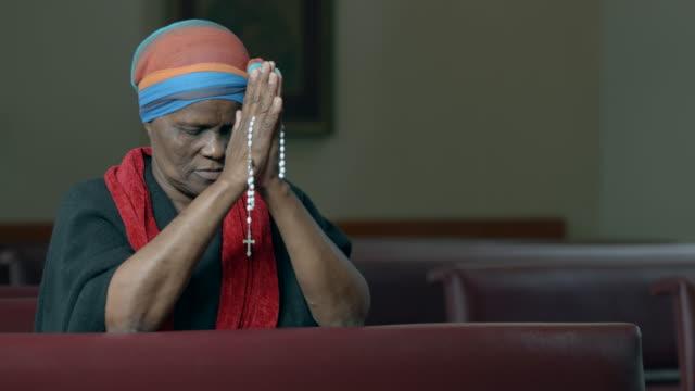 vídeos y material grabado en eventos de stock de mujer africana sosteniendo el rosario y orar. - misa