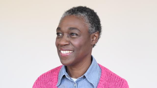 afrikansk kvinna i hennes 50-talet med kort hår att övergå till ansikte kameran i studion - mature women studio grey hair bildbanksvideor och videomaterial från bakom kulisserna