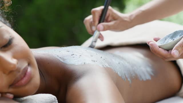 african woman receiving mud spa treatment - zabieg spa filmów i materiałów b-roll