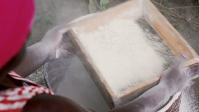 キャッサバ粉をふるいにかけているアフリカの女性 ビデオ
