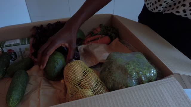 African Woman Taking Out Groceries Out Of Box