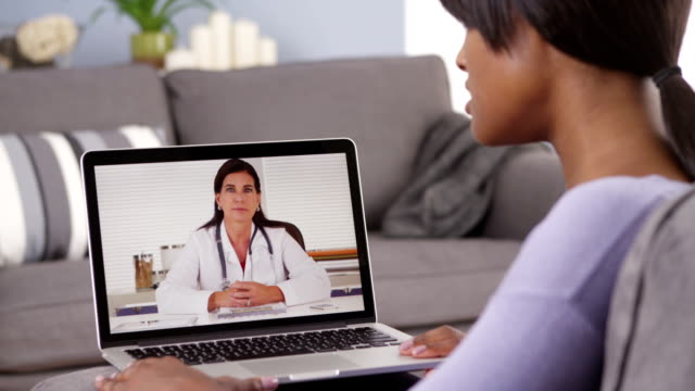 African woman video chatting with doctor video