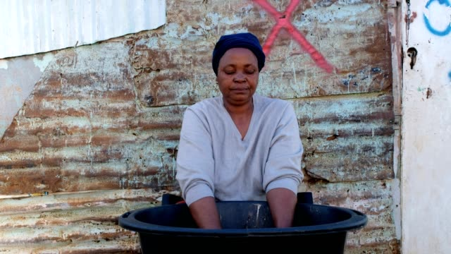 African woman washing her clothes An African woman sits and washes her clothes outside her shack in a bucket, Kayamandi South Africa western cape province stock videos & royalty-free footage