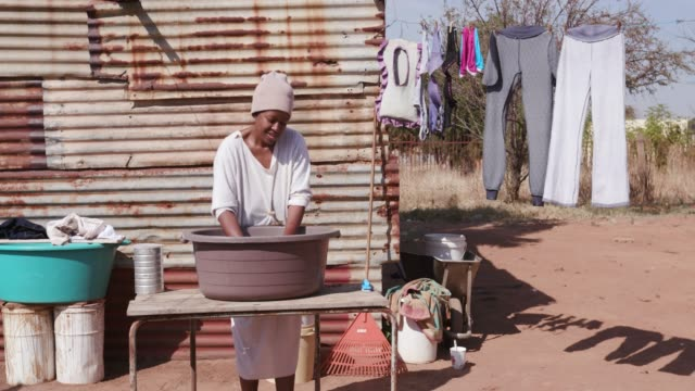 African woman without running water doing laundry in a bucket in front of her tin shack home video