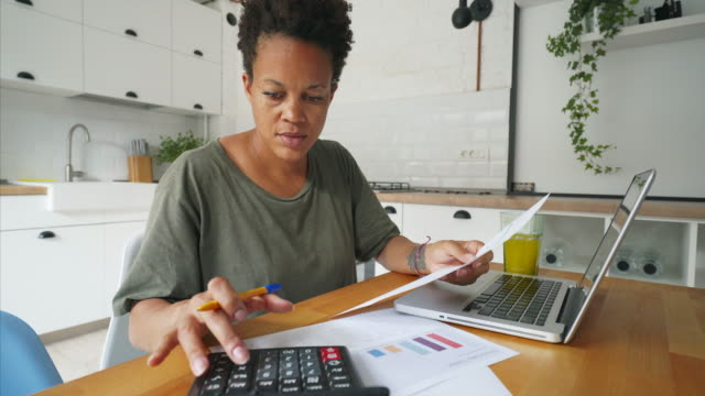 African woman working at home. African young woman working at home in the kitchen. She is calculating and forecasting the budget for next year and planning her new projects. individuality stock videos & royalty-free footage