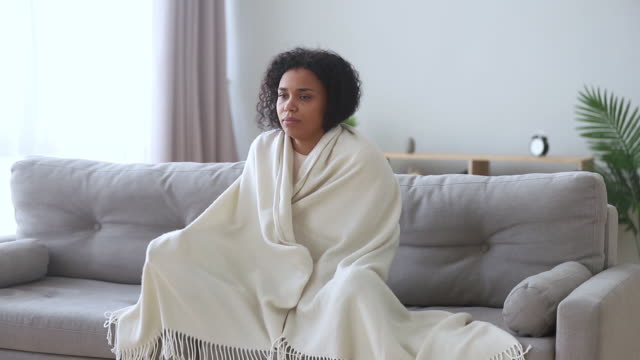 African woman wrapped in plaid shivers with cold at home