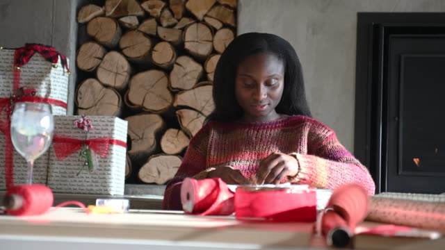 african woman wrapping gifts - avvolto video stock e b–roll
