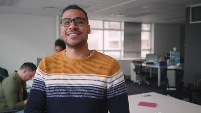 African young businessman standing in office with his arms crossed looking at camera with diverse colleagues talking in background Businessman crossing his arms in front of his business team arm stock videos & royalty-free footage
