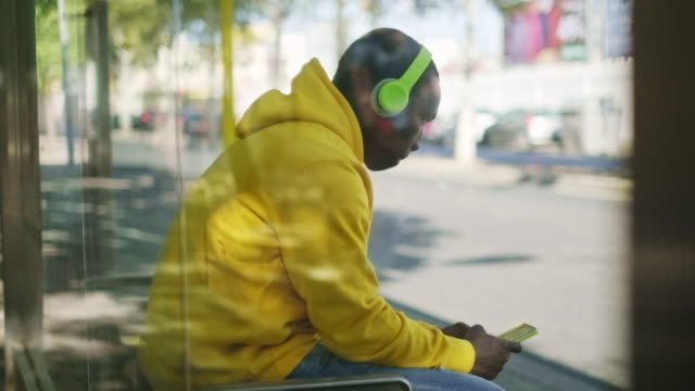 African Young Man Listening To Music At Bus Stop Young African Man With Wireless Headphones Streaming Music On Telephone, Sitting At Bus Stop And Waiting For Public Transportation. bus stop stock videos & royalty-free footage