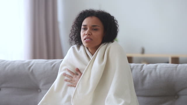 African young woman covered with plaid sit on sofa shivering African american young woman covered with plaid sit on sofa shivering freeze feel cold at home, ill mixed race female wrapped in blanket suffer from with no central heating problem in winter season shivering stock videos & royalty-free footage