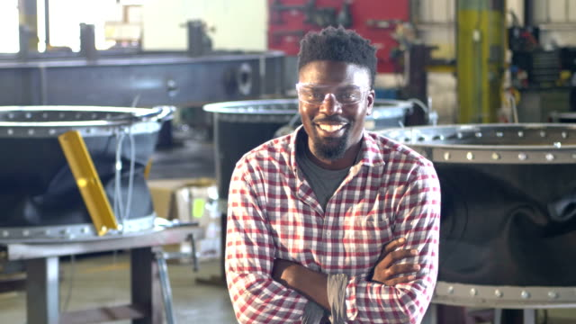 African-America man working in metal fabrication plant A mid adult African-American man in his 30s working in a metal fabrication plant. He is standing in the foreground, wearing safety glasses, looking at the camera with arms crossed. He is serious and then begins to smile. metal worker stock videos & royalty-free footage