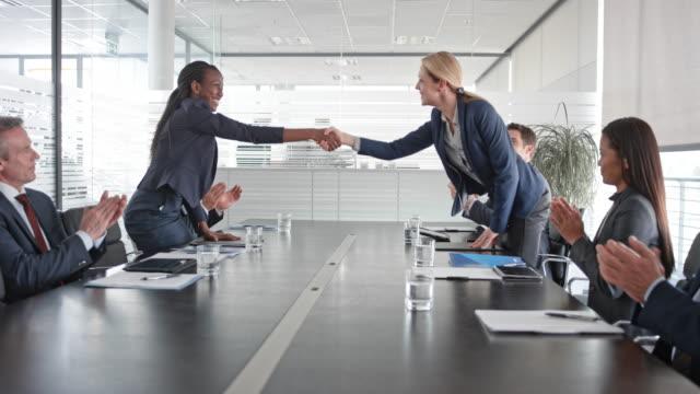 Femme d'affaires afro-américain et du Caucase se serrant la main après avoir signé un contrat en face de leurs équipes de projet dans la salle de conférence - Vidéo