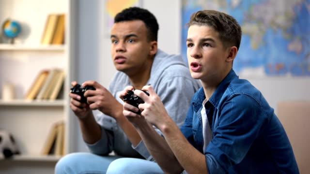 ragazzi afro-americani ed europei felici di vincere l'attività del tempo libero dei videogiochi - gioco d'azzardo video stock e b–roll