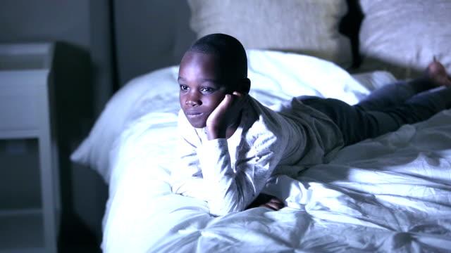 stockvideo's en b-roll-footage met afrikaans-amerikaanse jongen in slaapkamer die tv let - lagere schoolleeftijd