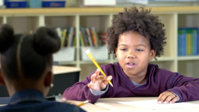 ragazzo afro-americano alle elementari, scrittura - 8 9 anni video stock e b–roll