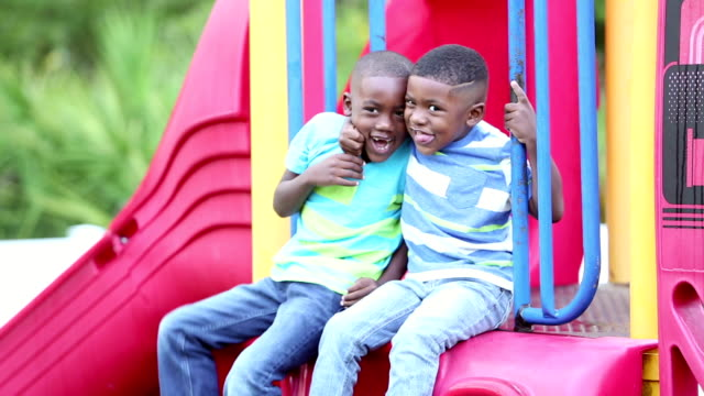 African-American brothers climbing on playground slide Two African-American brothers climbing up on playground equipment. They sitting down together smiling at the camera, and hug each other. They are 4 and 5 years old. only boys stock videos & royalty-free footage