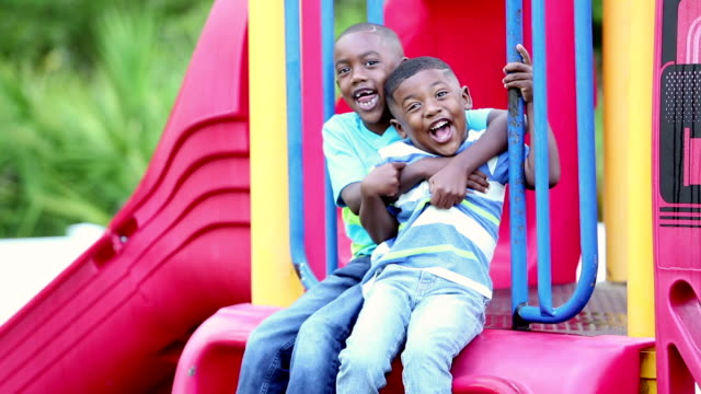 African-American brothers climbing on playground slide Two African-American brothers climbing up on playground equipment. They sitting down together smiling at the camera, and hug each other, making faces. They are 4 and 5 years old. only boys stock videos & royalty-free footage