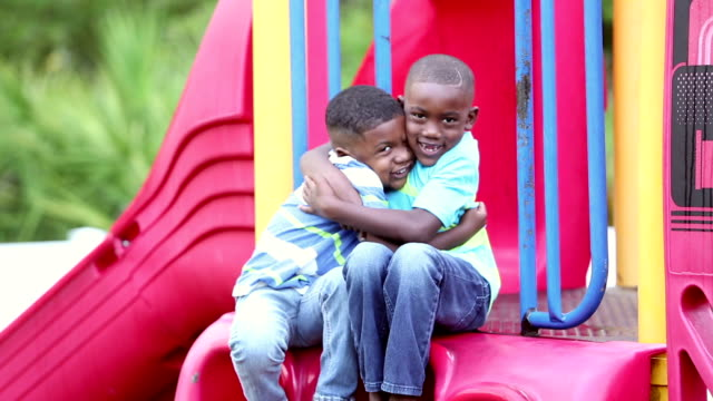 African-American brothers sitting on slide, hugging Two African-American brothers sitting together on a slide, smiling at the camera, being playful and silly. They hug each other. They are 4 and 5 years old. only boys stock videos & royalty-free footage