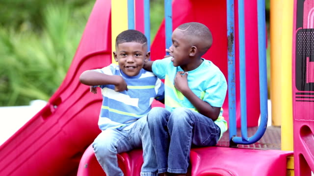 African-American brothers sitting on slide Two African-American brothers sitting together on a slide, smiling at the camera. They are each pointing to themselves and nodding their heads. They are 4 and 5 years old. only boys stock videos & royalty-free footage