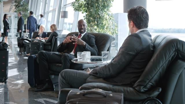 stockvideo's en b-roll-footage met ds afro-amerikaanse zakenman en zijn collega van de kaukasische praten in de business lounge op de luchthaven - vliegveld vertrekhal