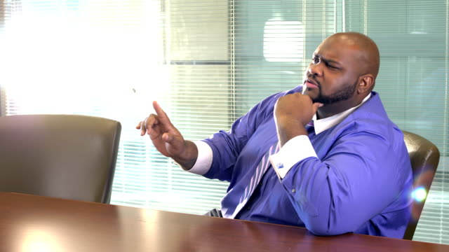 African-American businessman in board room talking A mature African-American man in his 40s sitting in an office board room. He is a well-dressed professional with a large build, confident and serious as he talks and listens with his hand on his chin. large build stock videos & royalty-free footage