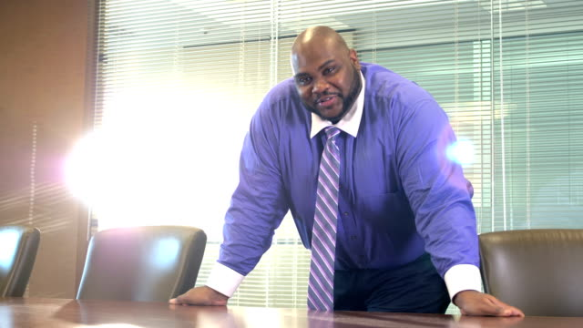 African-American businessman in board room A mature African-American man in his 40s standing in an office board room, rests his hands on the table and looks at the camera. He is a well-dressed professional with a large build. He is serious, smiling a little, as he talks. leaning stock videos & royalty-free footage