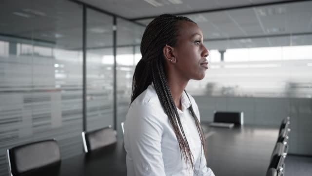 African-American businesswoman gazing out the window in an empty conference room video