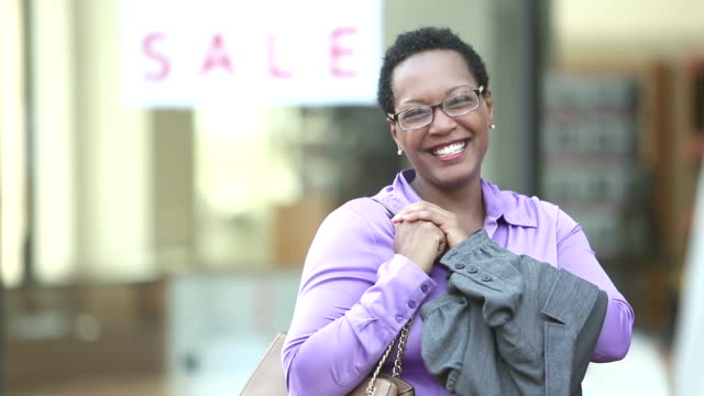 african-american businesswoman in city smiling at camera - quarantenne video stock e b–roll