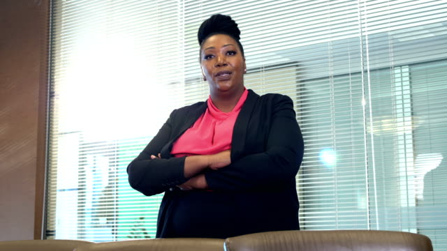 African-American businesswoman talking in board room A mid adult African-American woman in her 30s standing in an office board room. She is a well-dressed professional, confident and serious as she looks at the camera and talks to the viewer with her arms crossed. plus size model stock videos & royalty-free footage