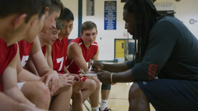 vídeos y material grabado en eventos de stock de afroamericano entrenador discutiendo una jugada con su equipo de baloncesto de la high school secundaria - deportes de la escuela secundaria