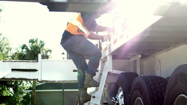 stockvideo's en b-roll-footage met afrikaans-amerikaanse bouwvakker klimmen op truck - ladder