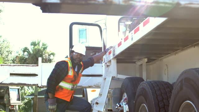 African-American construction worker climbing onto truck