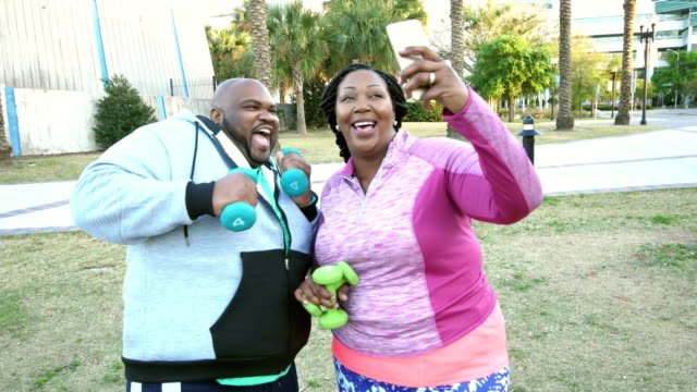 African-American couple exercising, taking selfie