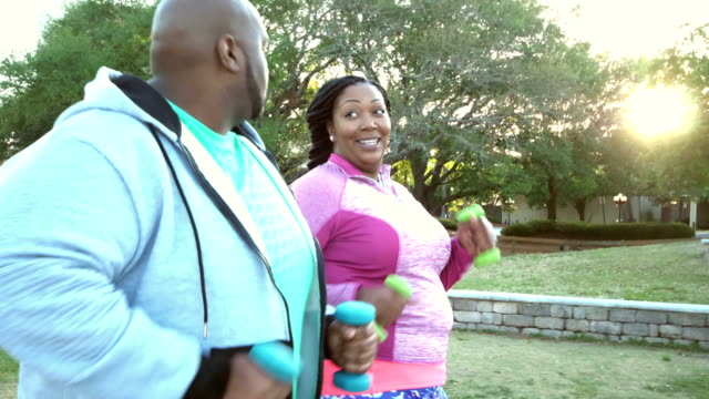 African-American couple power walking in city park