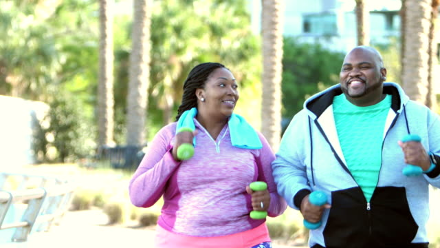 African-American couple power walking in park