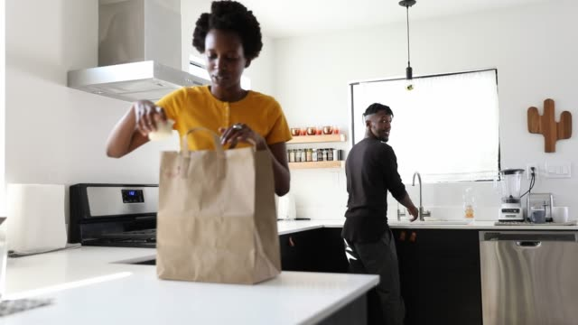 African-american couple working in the home kitchen preparing lunch