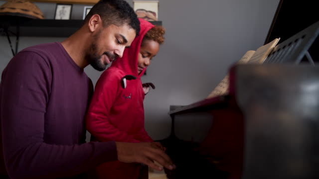 vídeos de stock e filmes b-roll de african-american dad learning his daughter how to play piano - instrumental