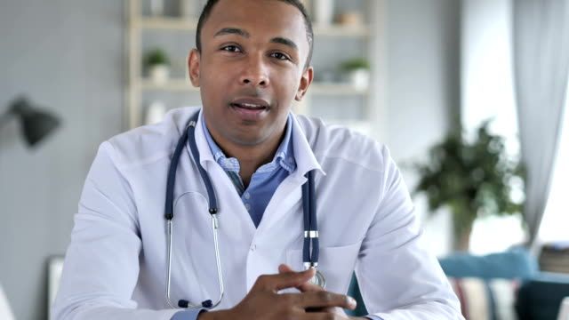 african-american doctor talking with patient, video chat - scambio d'idee video stock e b–roll