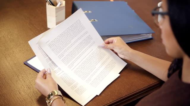 African-american entrepreneur in eyeglasses reading contract in office