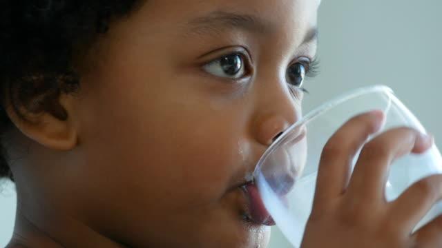 vídeos de stock, filmes e b-roll de afro-americano etnia menino beber leite de caneca - consciência negra