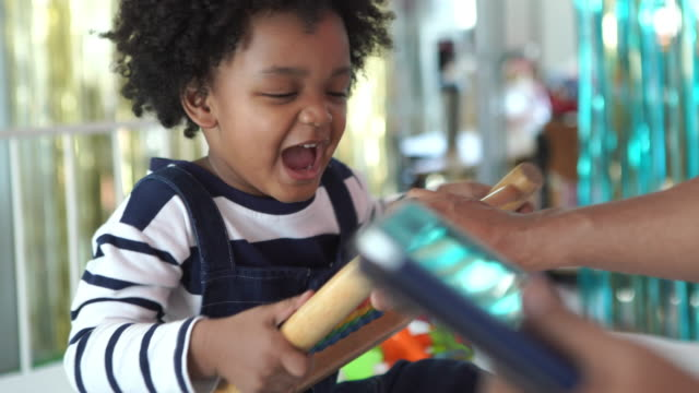 African-American Ethnicity little boy learning by doing at home with parent , homeschooling concept , Scramble for toys and selfishness boy - vídeo