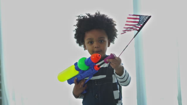 African-American Ethnicity little boy playing squirt gun and hollding American flag - vídeo