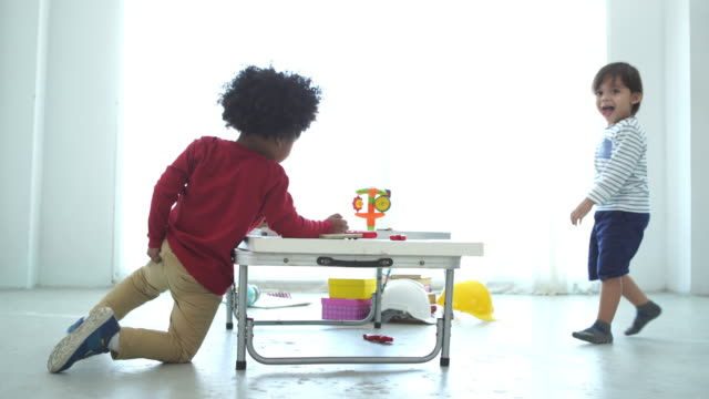 African-American Ethnicity little boy playing toy block with his friend , One boy have problem about his diaper , Scratching