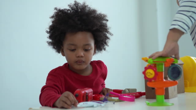 African-American Ethnicity little boy playing toy block with his friend