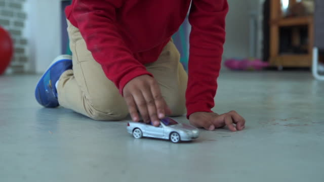 African-American Ethnicity little boy playing toy car