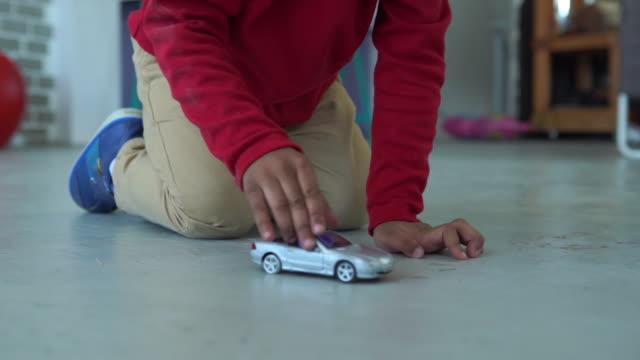 bambino di etnia afroamericana che gioca a fare l'auto giocattolo - giocattolo video stock e b–roll