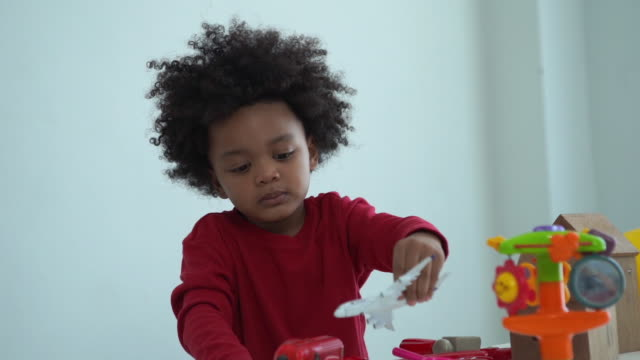 African-American Ethnicity little boy playing toy , imagine , aiming about airplane engineer - vídeo