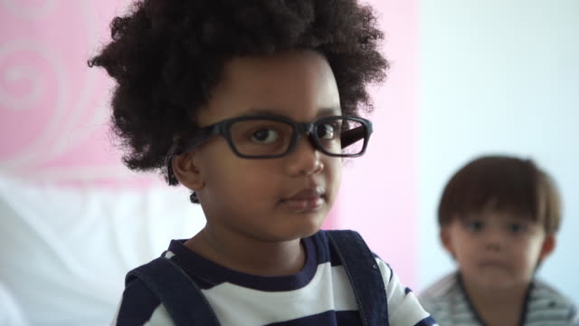 Afro-americano Etnia menino tring para usar óculos e estetoscópio médico - vídeo