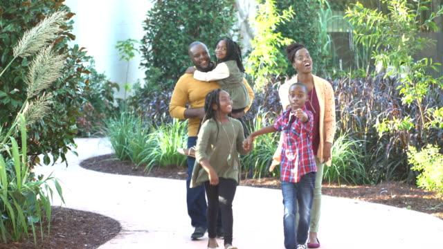 afroamerikansk familj om fem promenader genom trädgården - mellan 30 och 40 bildbanksvideor och videomaterial från bakom kulisserna